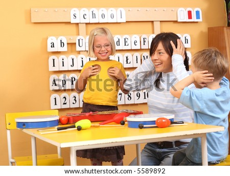 teacher and two preschoolers playing with instruments