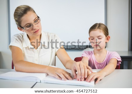 Teacher assisting blind student in library at school #454727512