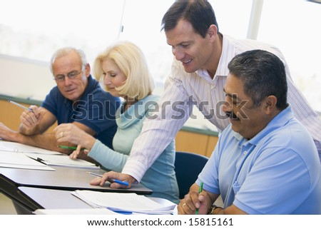 Teacher assisting mature student in class