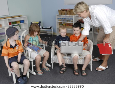 Teacher assists children with a work on the laptop computer at the preschool class.