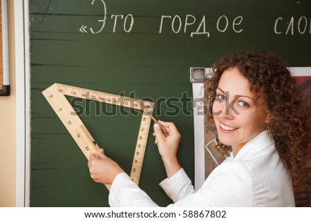 Teacher at blackboard with ruler and pencil in hand. Smiling, she looks into camera.
