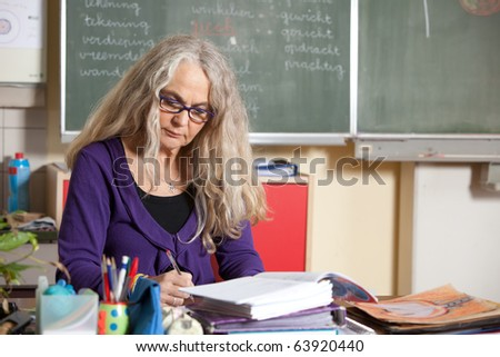 Teacher at her desk in class checking on the homework