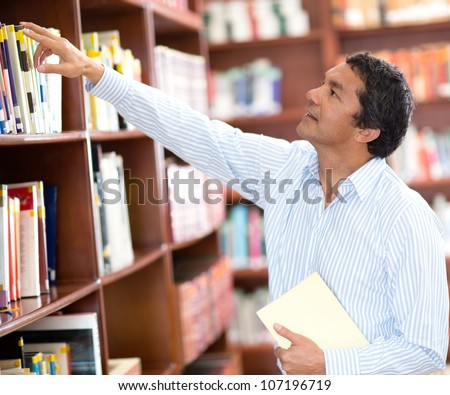 Teacher at the library looking for a book in the bookshelves