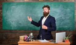 Teacher bearded man tell interesting story. Teacher charismatic hipster stand near table classroom chalkboard background. Teacher interesting interlocutor best friend. Talking to students or pupils.