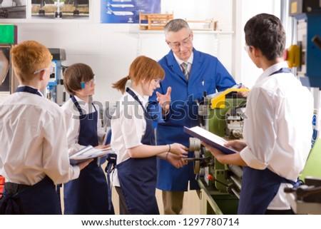 Teacher demonstrating lathe to high school pupils in metalwork class #1297780714