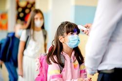 Teacher doing temperature check on school children