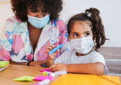 Teacher draws with little girl while wearing surgical face mask - Safety measures