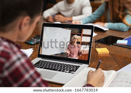 Teacher explaining lesson in video call while girl taking notes. Rear view of university student understanding concepts online while making notes. Young woman studying on computer and writing on notes