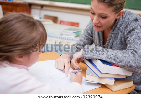 Teacher explaining something to her pupil in a classroom