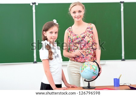 teacher explains the lesson in geography, stand near the school globe