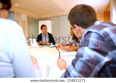 Teacher giving business presentation to students - stock photo
