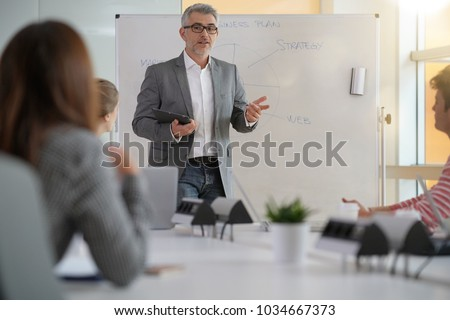 Teacher giving economics class, using whiteboard