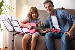 Teacher guitar with his student looking at the camera sitting on a sofa in her living room