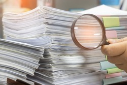 Teacher hand holding magnifier is searching for student's homework assignment archive with colorful paper on desk in office to make check. Stack of paperwork and report. Education and business concept