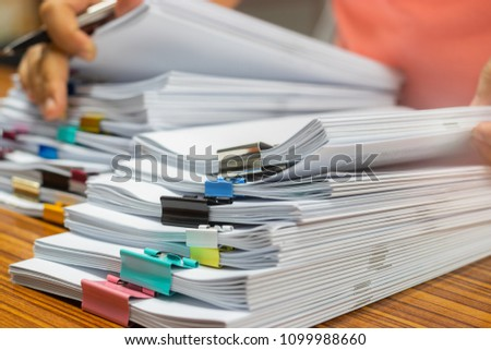Teacher hand holds pen for checking student's homework assignment on table office. Paper documents stacked in archive with paperclip. Report papers stacks. Business and education concept.