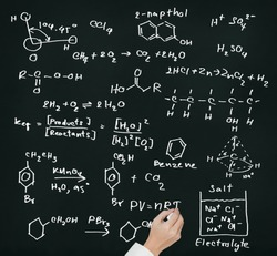 teacher hand writing science and chemical formula on chalkboard