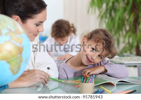 Teacher helping a pupil with her school work