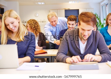 Teacher helping a student with laptop computer in a class in school