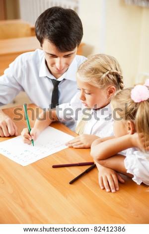 Teacher helping elementary school pupils with their tasks