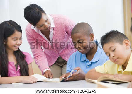 Teacher helping elementary school reading group