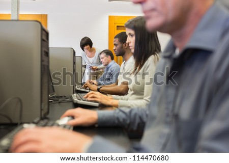 Teacher helping her students in computer class in college