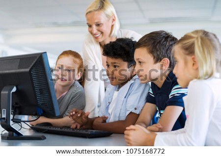 Teacher helping multiethnic children at computer terminal in primary school. Smiling school kids using computer with teacher in library. Happy mature woman and elementary students using desktop pc.