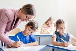 Teacher helping pupils studying and writing. Lesson for kids at elementary school. Children sitting at desk in classroom. Woman teaching primary students. Back to school concept.