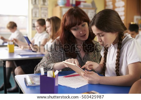 Teacher helping schoolgirl using a tablet computer in class