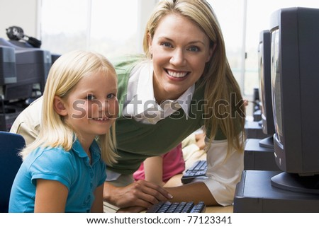 Teacher helping student at computer terminal with students in background (depth of field/high key)
