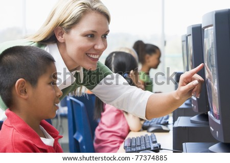 Teacher helping student at computer terminal with students in background (selective focus/high key)