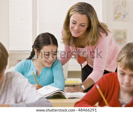 Teacher helping student in classroom