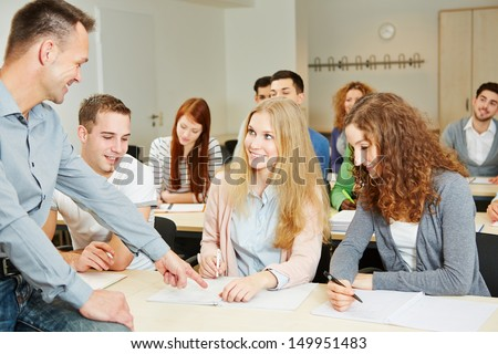Teacher helping students in university seminar class