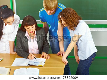 Teacher helping students who are standing around her in school classroom.
