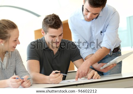 Teacher helping students with assignment