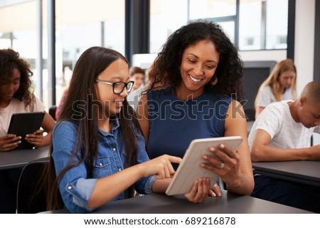 Teacher helping teenage schoolgirl with tablet computer
