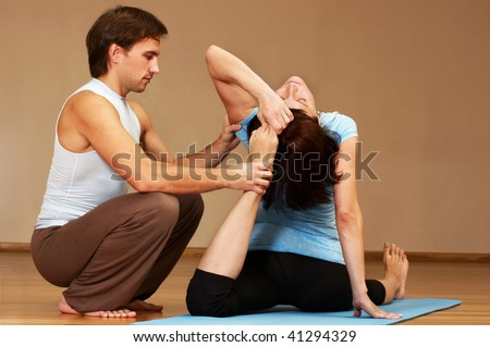 teacher helping with yoga pose indoors
