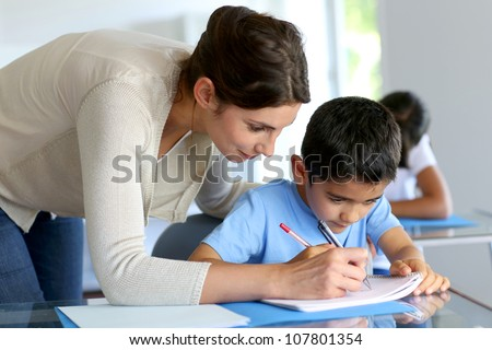Teacher helping young boy with writing lesson #107801354