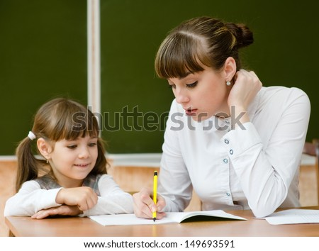 Teacher helping young girl with writing lesson