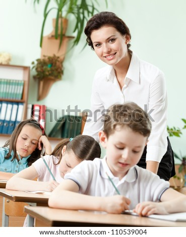 Teacher helps her pupils to do the task at school