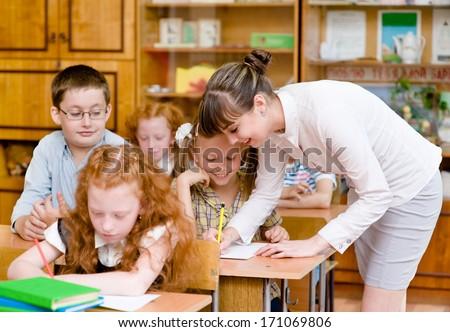 Teacher helps the schoolkids with schoolwork in classroom - stock photo