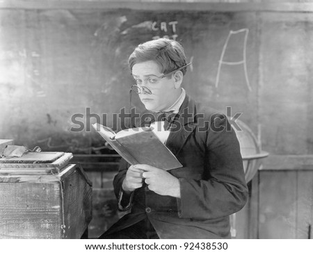 Teacher holding a book in front of a black board