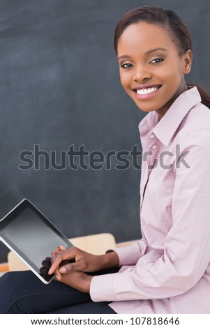 Teacher holding a tablet computer while smiling in a classroom