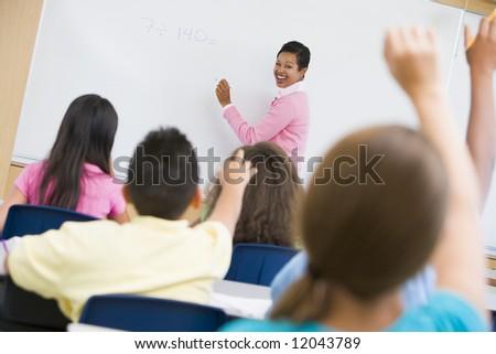 Teacher holding elementary school maths class