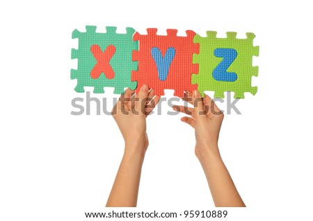 teacher holding in the hand the amusing colored educational puzzles with alphabet