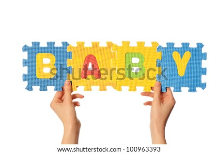 teacher holding in the hand the amusing colored educational puzzles with the word baby