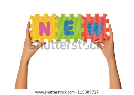 teacher holding in the hand the amusing colored educational puzzles with the word news