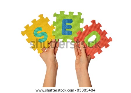 teacher holding in the hand the amusing colored puzzles with word SEO - stock photo