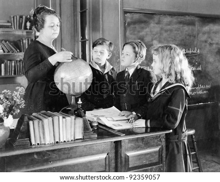 Teacher in a classroom with three pupils pointing to a globe - stock photo
