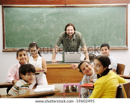Teacher in classroom with his little happy students