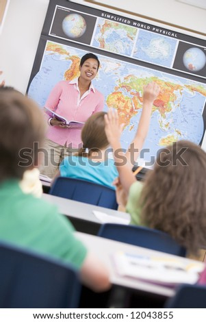 Teacher in elementary school geography class answering questions - stock photo